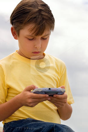 Playing a Game stock photo, Child playing games on a portable player by Leah-Anne Thompson
