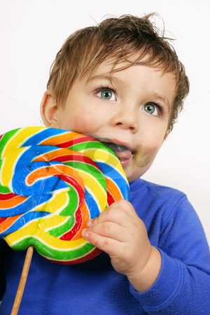 Child eating a large lollipop stock photo, A young child eating a very large lollipop candy on a stick by Leah-Anne Thompson