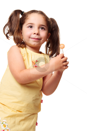 Little girl in ponytails holding a lollipop stock photo, Little girl dressed in yellow is holding a sweet lolly by Leah-Anne Thompson