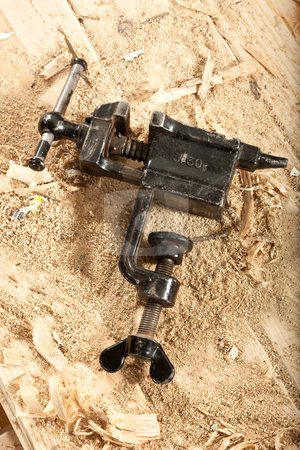 Grip vice stock photo, Tools series: steel black grip vice on sawdust table by Gennady Kravetsky