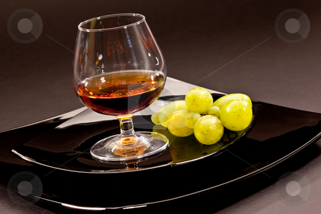 Brandy stock photo, Drink series: glass of cognac grapes on the black plate by Gennady Kravetsky
