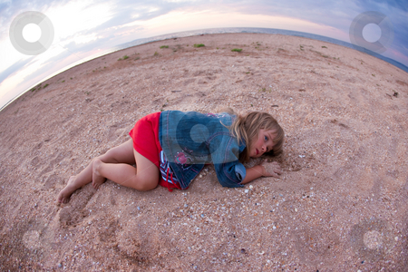 Little girl on beach stock photo, People series: little girl are lay on sea sand by Gennady Kravetsky
