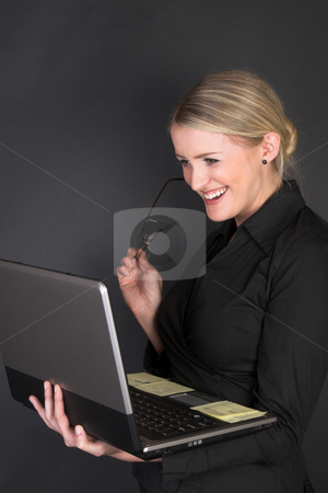 Beautiful Businesswoman stock photo, Composed Businesswoman holding a laptop against a black background by Carla Booysen
