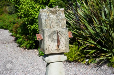 Sundial stock photo, Old sundial in a garden by Jaime Pharr