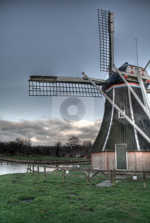 Dutch Windmill in Autumn stock photo, A HDR picture of a dutch windmill in Autumn. The picture has been taken from the back of the mill. On the horizon, a approaching gathering of clouds is visible by Tijs Zwinkels
