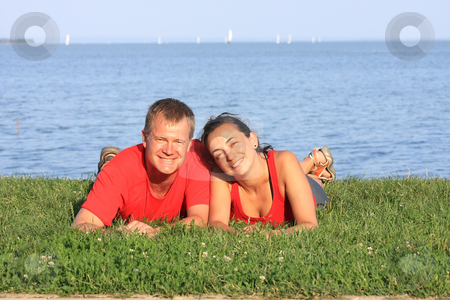 Young couple stock photo, Joyful young pair is overlaping shore of the lake by ARPAD RADOCZY