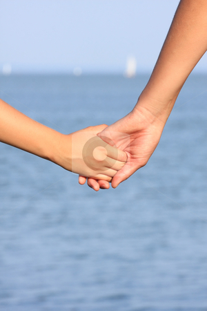 Handshake stock photo, A mother and girl are standing hand since on the coast by ARPAD RADOCZY