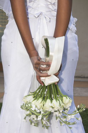 Beautiful Bride stock photo, African Bride holding cream floral bouquet behind her back by Carla Booysen