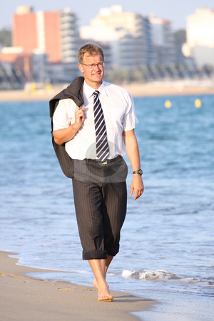 Businessman stock photo, Happy young man walks close to the sea by ARPAD RADOCZY