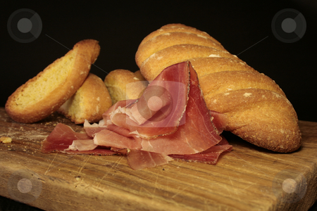 Bread and speck stock photo, Handmade bread and sliced speck on cutting board by Marina Magri