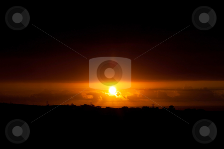 Sunset during summertime in Mauritius. stock photo, Sunset is the daily disappearance of the sun below the horizon as a result of the Earth's rotation. The atmospheric conditions created by the setting of the sun, occurring before and after it disappears below the horizon, are also commonly referred to as