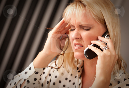 Blonde Woman on Cell Phone with Stressed Look stock photo, Blonde Woman on Her Cell Phone with Stressed Look on Her Face. by Andy Dean