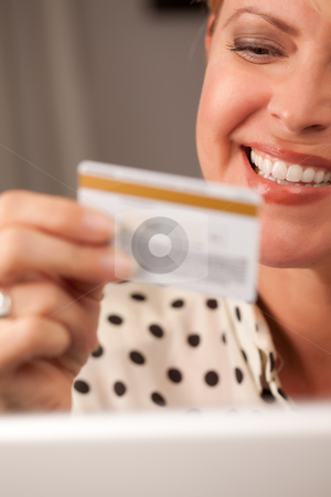 Beautiful Woman Using Laptop Holding Her Credit Card stock photo, Beautiful Woman on Her Laptop Holding Her Credit Card. by Andy Dean