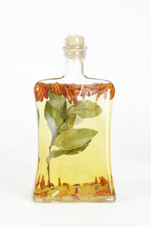 Oil bottle stock photo, A glass bottle filled with grapeseed oil, garlic, chilli peppers and bay leaves. by Leah-Anne Thompson