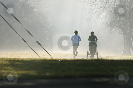 Misty runners stock photo, Two joggers one with a baby stroller exercise despite the misty fog. by Leah-Anne Thompson