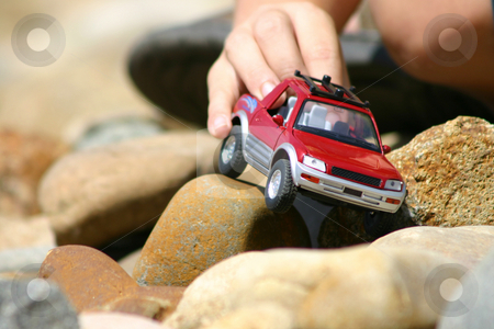 Boy playing with toy car stock photo, A coy plays with a toy car over rocks by Leah-Anne Thompson