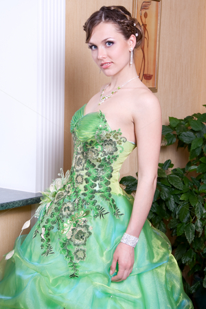 Woman in a green dress stock photo, Woman in a green dress posing in the interior by Artem Zamula