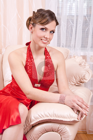 Woman in a red dress stock photo, Woman in a red dress posing in an armchair by Artem Zamula