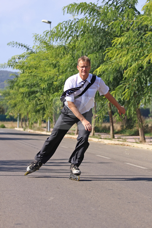 Businessman stock photo, Young businessman go to work with a roller skate by ARPAD RADOCZY