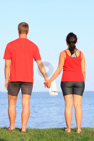 Young couple stock photo, A young couple looks at the sailboat by ARPAD RADOCZY