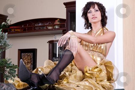 Woman in a aureate dress stock photo, Woman in a aureate dress posing in the interior by Artem Zamula