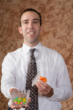 Businessman Offering Candy stock photo, A young businessman offering some candy from a glass dish by Richard Nelson