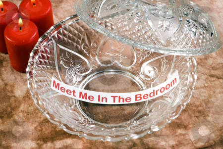 Erotic Memo stock photo, An erotic memo left inside a glass candy dish with some red candles bruning beside it by Richard Nelson