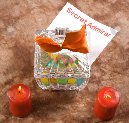 Secret Admirer Note stock photo, A note from a secret admirer is placed inside a candy dish beside two burning candles by Richard Nelson
