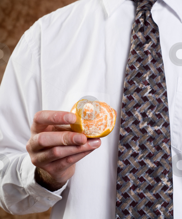 Businessman Showing Orange stock photo, Closeup view of a businessman showing a partially peeled orange by Richard Nelson