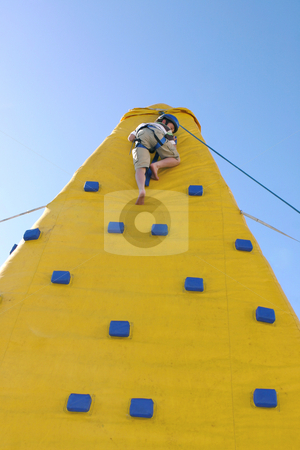 Child coming down from a climbing wall stock photo, A boy makes the jouney down from the top of a climbing wall. by Leah-Anne Thompson