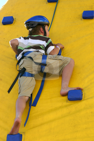 Child climbing a climbing wall stock photo, A brave child climbs up a climbing wall. by Leah-Anne Thompson