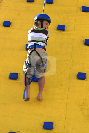 A child abseilling down a climbing wall stock photo, Abseilling down a climbing wall by Leah-Anne Thompson