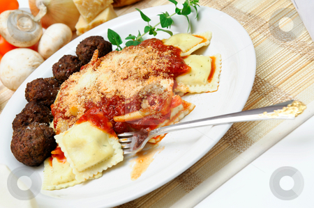 Ravioli stock photo, Ravioli topped with spaghetti sauce and Parmesan cheese with meatballs on the side served on a white plate garnished with a sprig of Oregano. by Lynn Bendickson