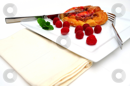 Raspberry Danish Pastry stock photo, Raspberry Danish pastry with fresh raspberries and a mint garnish served on a square white plate with fork, knife and a cloth napkin by Lynn Bendickson