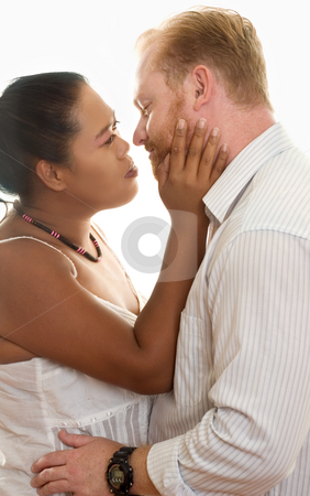 Mixed Race Embrace stock photo, Mixed race couple look lovingly into one another eyes by Leah-Anne Thompson