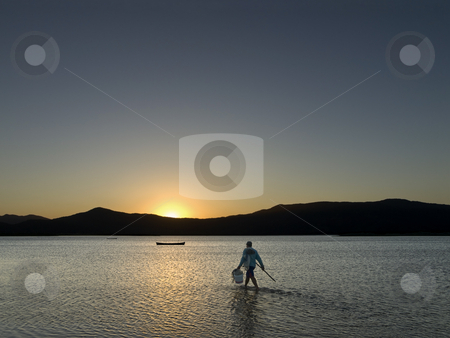 The way of the fisherman stock photo, An unrecognizable fisherman walks through the shallow lake to reach his boat on the magic hour. by Ignacio Gonzalez Prado