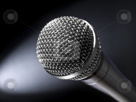 Microphone on stage stock photo, A dynamic microphone on stage. Bright spot light on the background. by Ignacio Gonzalez Prado