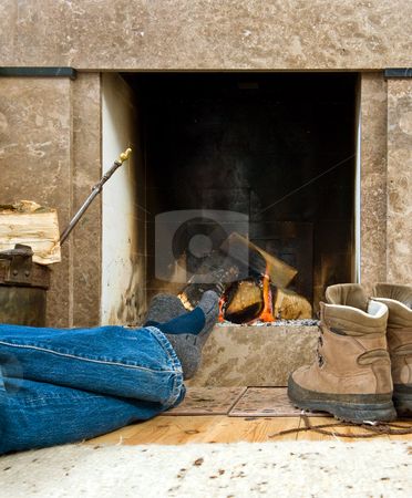 Hiker resting by the fireplace stock photo, Hiker warming uyp and relaxing by a small fireplace by Corepics VOF