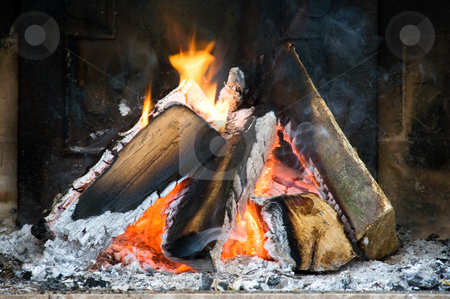 Fireplace stock photo, Several logs burning in a small fireplace surrounded by ashes, smoke and flames by Corepics VOF