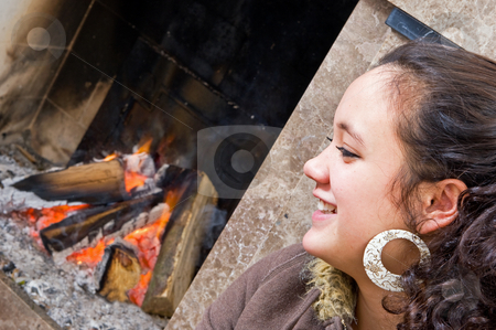 Young woman by the fire stock photo, Young woman sitting by the fire during a game of cards by Corepics VOF