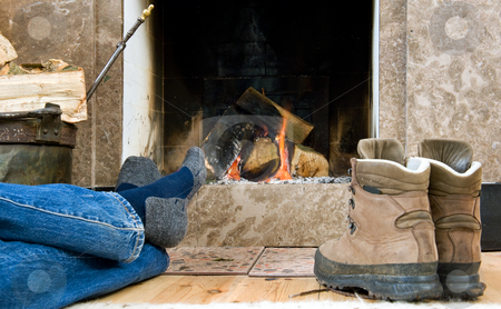 Hiker resting by the fireplace stock photo, Hiker warming up and relaxing by a small fireplace by Corepics VOF