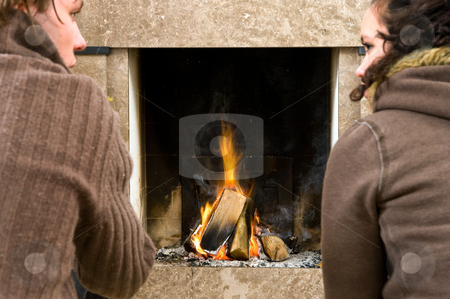 By the fireplace stock photo, Young couple enjoying the warmth of a fire. Focus on the fireplace by Corepics VOF