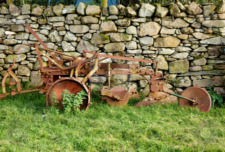 Old rusty plow in shadow of stone wall stock photo, Iron plough abandoned by a dry stone wall by Steven Heap