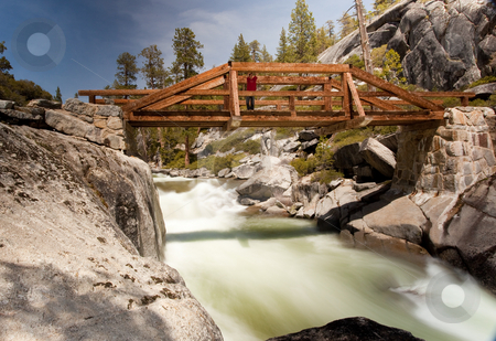 Bridge over Yosemite river on top of falls stock photo, Slow motion photo of Yosemite Falls river with male hiker on the bridge by Steven Heap