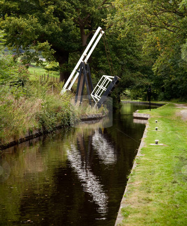Open bridge over still canal stock photo, Canal in England with a bridge open to boat traffic by Steven Heap