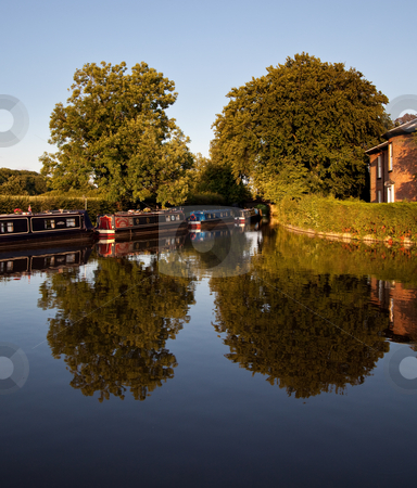 Canal barges reflected in the water stock photo, Calm view of the canal near Ellesmere with the barges reflected in the water by Steven Heap