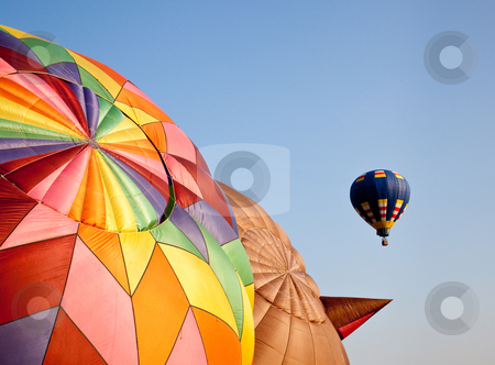 Hot air balloon in the air above two others stock photo, Single hot air balloon soaring into the sky above two others being inflated on the ground by Steven Heap