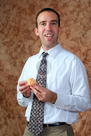 Businessman Having Orange For Snack stock photo, A businessman wearing a tie is going to eat a peeled orange for a snack by Richard Nelson