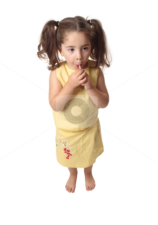 Girl sucking on a lollipop candy stock photo, A small preschool girl eating a sweet lollipop.  She is barefoot and wearing a skirt and top with hair in ponytails. by Leah-Anne Thompson