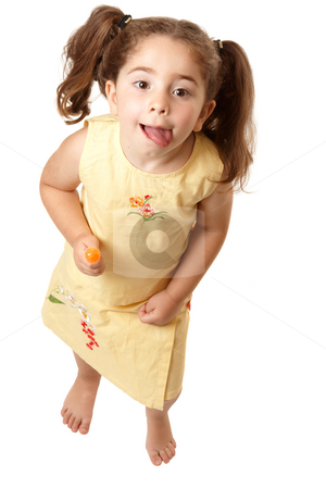 Adorable girl looking up and licking lips stock photo, Above view of a young girl child standing  and licking her lips. by Leah-Anne Thompson